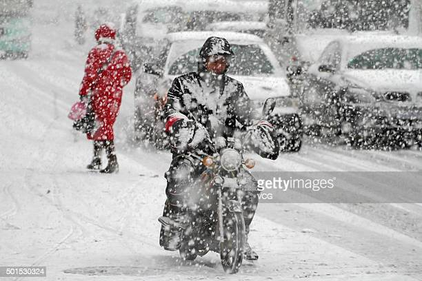 A man rides on a motorbike in snow on December 16 2015 in Yantai Shandong Province of China Yantai Weather Bureau has issued yellow alert to ice road...