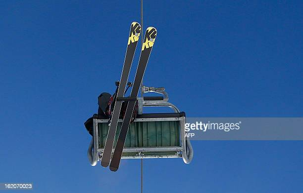 A man rides on a ski lift with his K2 ski on a sunny day in wintry Lech am Arlberg western Austria on February 18 2013 AFP PHOTO / ALEXANDER KLEIN