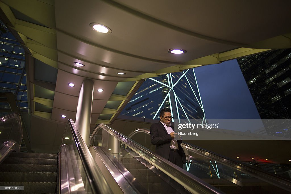 A man rides on an escalator in the central business district of Hong Kong, China, on Friday, Jan. 4, 2013. Hong Kong topped the ranks as the most expensive office market by total occupancy cost, according to a report by CBRE Research released on Jan. 7. Photographer: Jerome Favre/Bloomberg via Getty Images
