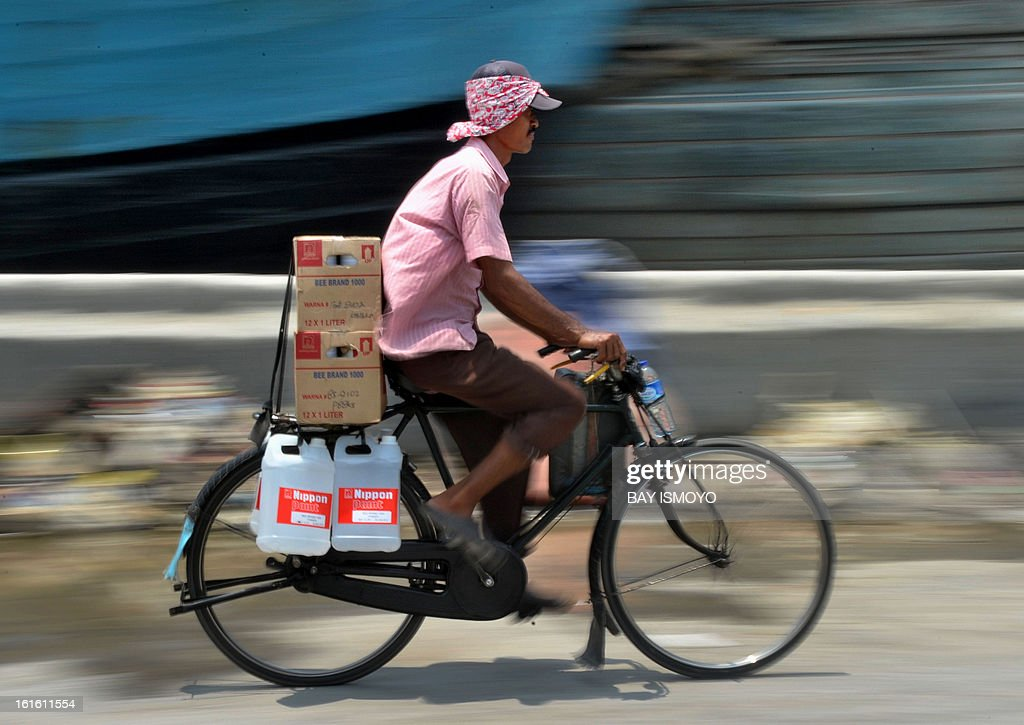 A man rides on his bicycle to deliver goods to customers at Jakarta's traditional port of Sunda Kelapa in Jakarta on February 13, 2013. Indonesia's central bank kept its key interest rate steady at 5.75 percent for the 12th straight month as it looks to boost growth in Southeast Asia's biggest economy. AFP PHOTO / Bay ISMOYO