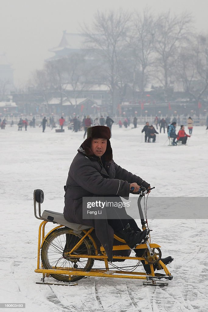 A man rides on specially constructed 'ice-bicycle' on the frozen Houhai Lake during severe pollution on February 3, 2013 in Beijing, China. Houhai Lake is a popular place for winter sport and entertainment in Beijing.