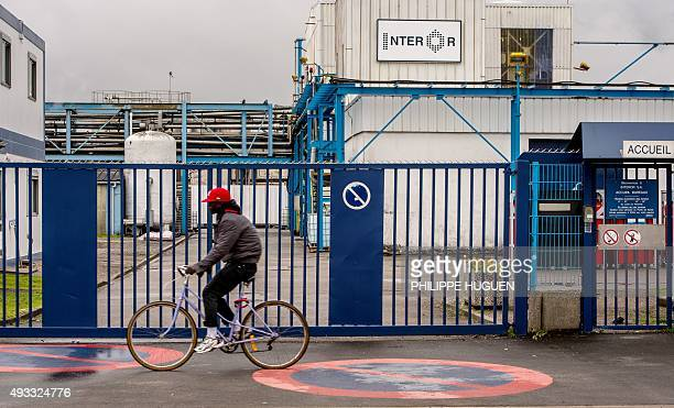 A man rides past a Interor chemical plant regulated by the Seveso directive on October 19 near the 'New Jungle' migrants camp in Calais where some...