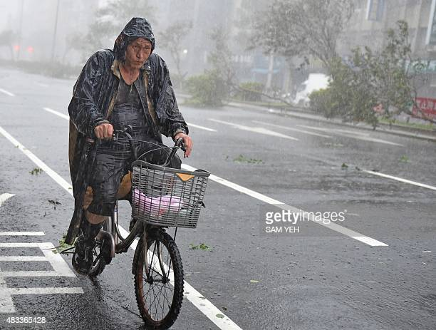 A man rides past damaged trees as typhoon Soudelor hits Taipei on August 8 2015 Typhoon Soudelor battered Taiwan with fierce winds and rain leaving...