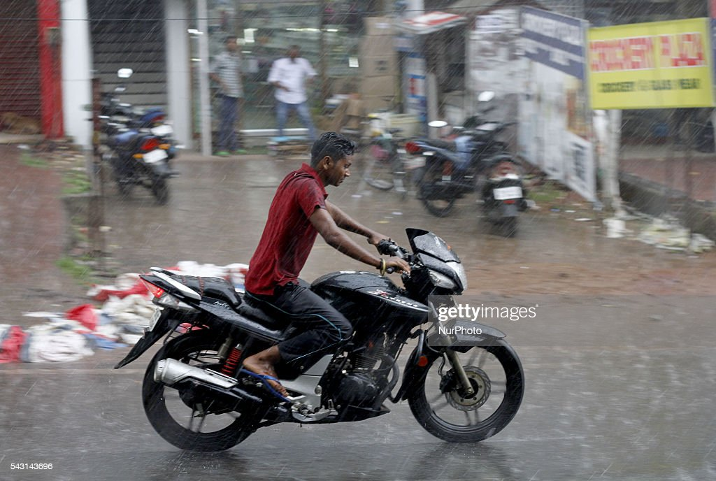 A man rides past his motor bike wade through in the monsoon rain in the eastern Indian city Bhubaneswar, India, Sunday, 26 June 2016.