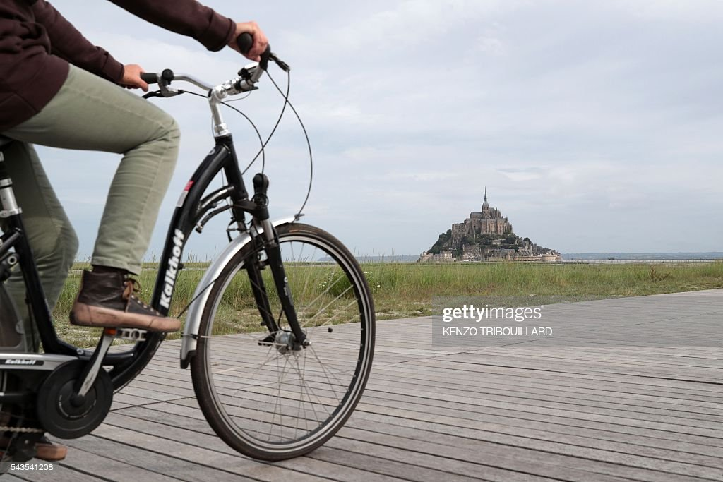 A man rides past Le Mont-Saint-Michel, on June 29, 2016, three days before the start of the 103rd edition of the Tour de France cycling race. The 2016 Tour de France will start on July 2 in the streets of Le Mont-Saint-Michel and ends on July 24, 2016 down the Champs-Elysees in Paris. / AFP / KENZO