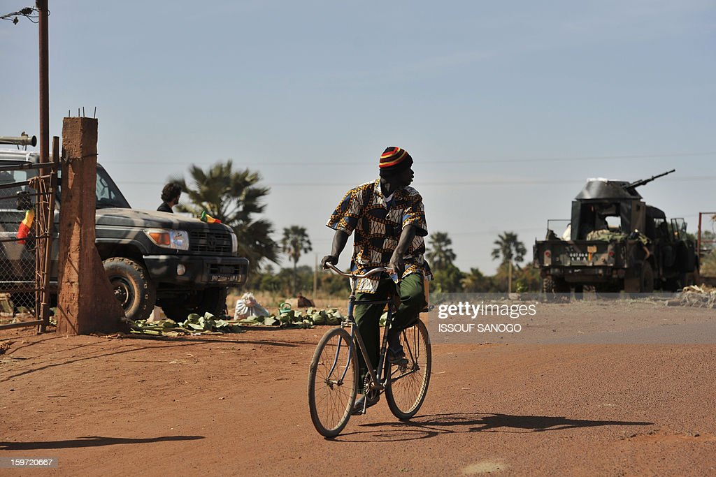 A man rides past Malian soldiers being deployed in the city of Niono on January 19, 2013. Ivorian President Alassane Ouattara on January 19 called for a broader international commitment to the military operations in Mali, where Malian and French forces are battling Islamist militant groups that control the country's vast arid north. Some 2,000 members of MISMA (the International Mission for Mali Assistance), the African intervention force, are expected to be deployed by January 26. About 100 soldiers from Togo and Nigeria have already arrived in Bamako, and another 30 or so from Benin are en route to join them.
