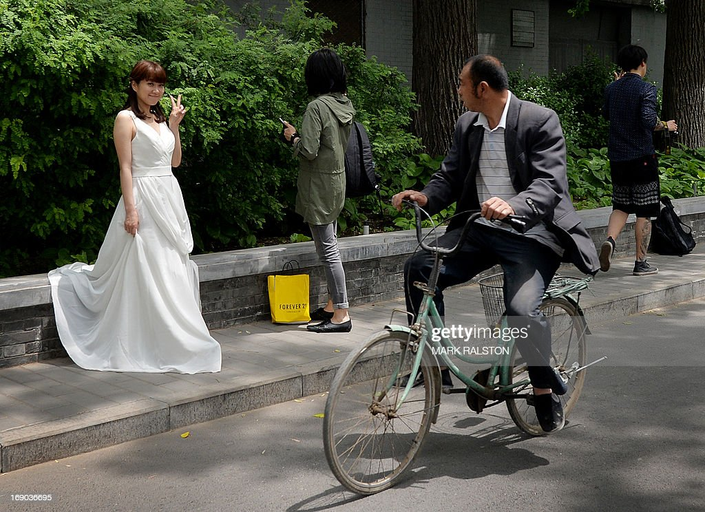 A man (R) rides past on a bicycle as a Chinese bride (L) poses for her wedding photos at Houhai Lake in Beijing on May 19, 2013. Beijing's parks and lakes provide a colourful backdrop for wedding photos during the spring weather, with some couples taking their photos six months before the actual wedding. AFP PHOTO / Mark RALSTON