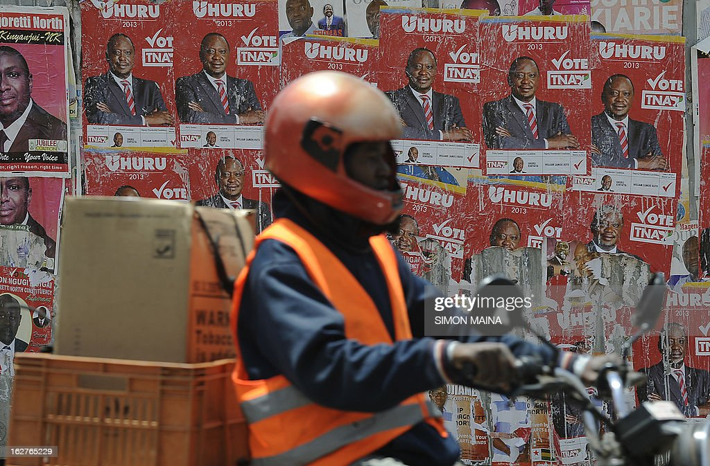 A man rides past posters supporting Presidential candidate Uhuru Kenyatta on February 26, 2013 in the sprawling Kibera slums. Kenya is gearing up for presidential, gubernatorial, senatorial elections on March 4, the first since bloody post-poll violence five years ago in which more than 1,100 people died after contested results. AFP PHOTO/SIMON MAINA