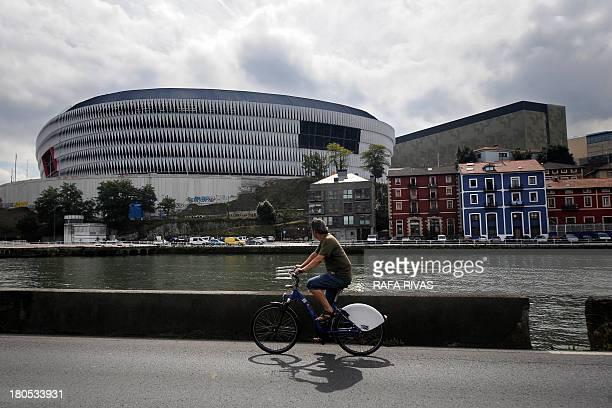 A man rides past the new San Mames football stadium in the Northern Spanish Basque city of Bilbao on September 14 2013 AFP PHOTO/ RAFA RIVAS