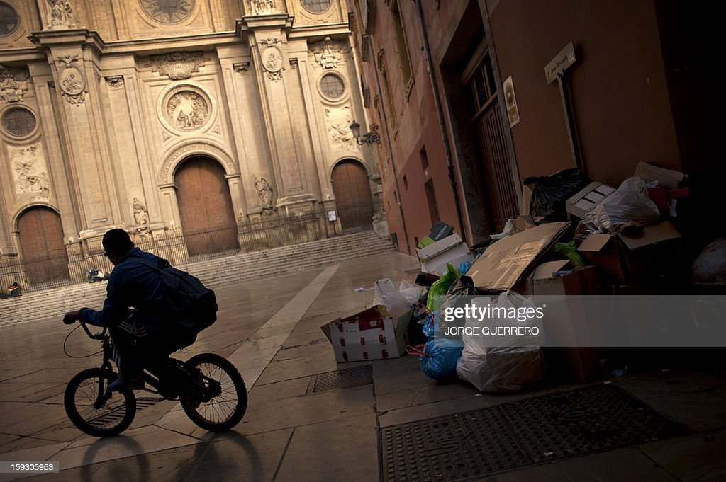 A man rides past uncollected rubbish in a street of Granada on January 11, 2013. Rubbish collectors have been on strike in the municipality of Granada to protest against the austerity cuts imposed by the town hall.