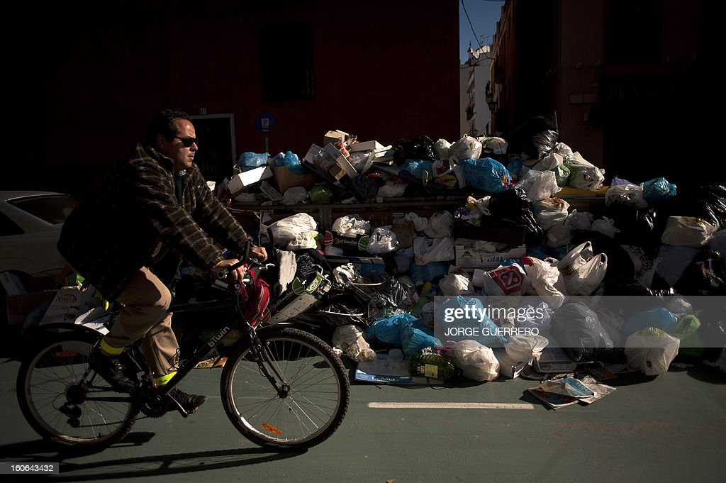 A man rides past uncollected rubbish in a street of Sevilla on February 4, 2013. Rubbish collectors have been on strike in the municipality of Sevilla to protest against the austerity cuts imposed by the town hall.