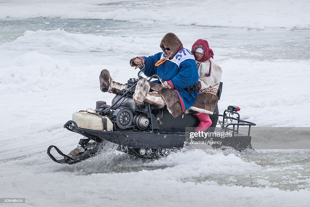 A man rides snowmobile as a woman hold on to him in melting snow at the north of Yamal Gyda, the northernmost settlement of the Yamalo-Nenets Autonomous Okrug in Russia on April 27, 2016. Effects of global warming are seen more clearly every year as north gets warmer and spring comes sooner. This situation makes residents and reindeer harders' life very difficult.