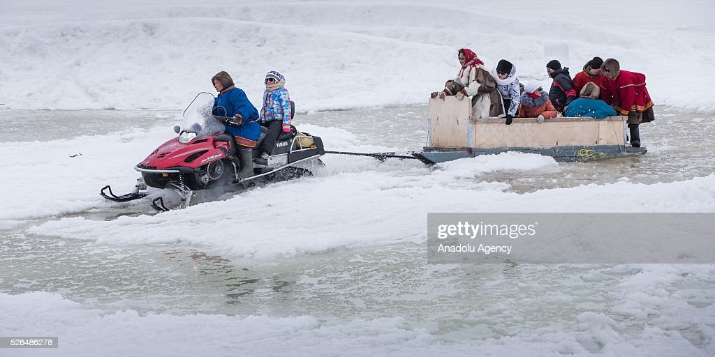 A man rides snowmobile as he carries people on sled in melting snow at the north of Yamal Gyda, the northernmost settlement of the Yamalo-Nenets Autonomous Okrug in Russia on April 27, 2016. Effects of global warming are seen more clearly every year as north gets warmer and spring comes sooner. This situation makes residents and reindeer harders' life very difficult.