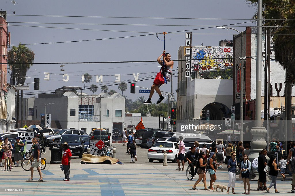 A man rides the Flightlinez zip line across the strand at Venice Beach in Los Angeles, California, U.S., on Wednesday, Aug. 14, 2013. Overall U.S. tourism-related sales increased 6.8% in the second quarter of 2013 as compared to 2012. Photographer: Patrick T. Fallon/Bloomberg via Getty Images