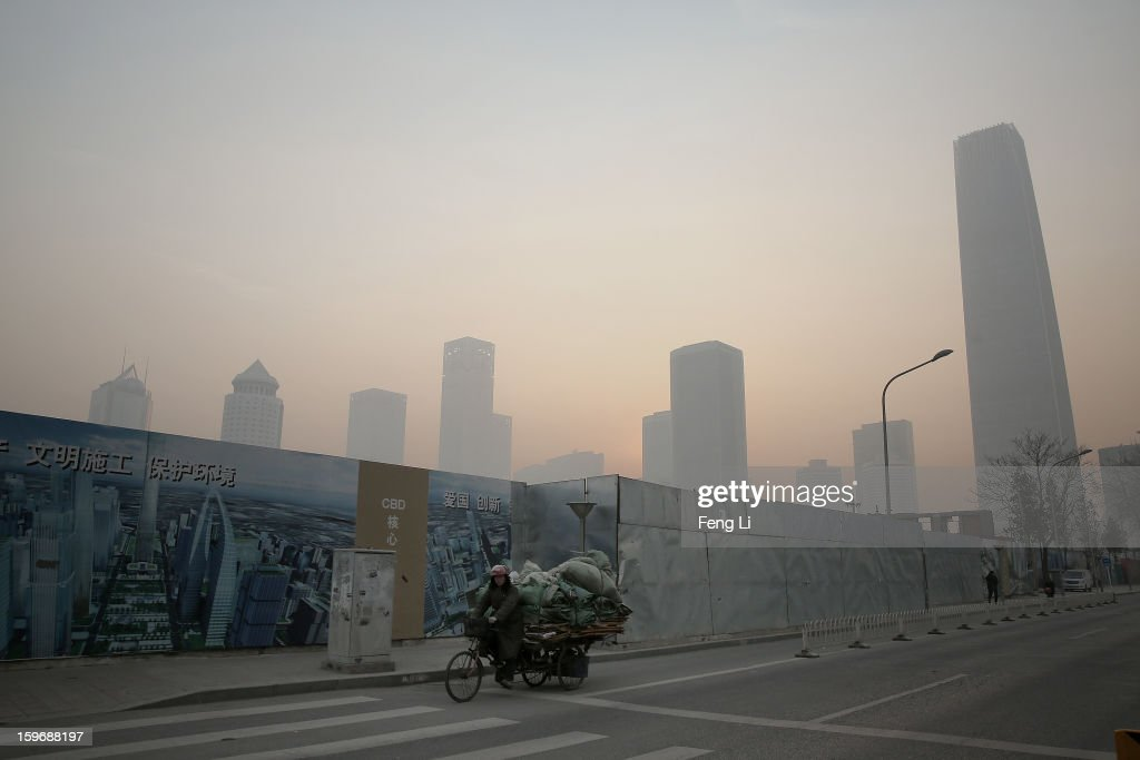 A man rides the tricycle passing the central business district during severe pollution on January 18, 2013 in Beijing, China.