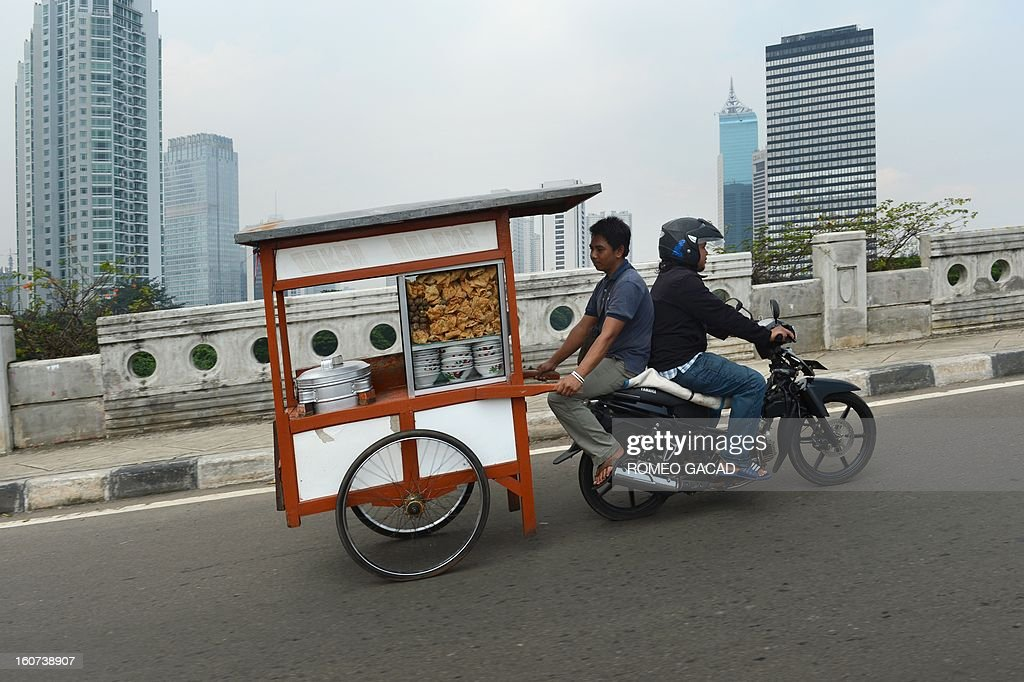 A man rides uphill on the back of a motorbike as he transports his food-vending cart in the business district of Jakarta on February 5, 2013. Indonesia said on February 5 that Southeast Asia's biggest economy grew 6.23 percent in 2012 , below expectations, supported by strong private consumption and investment. AFP PHOTO / ROMEO GACAD