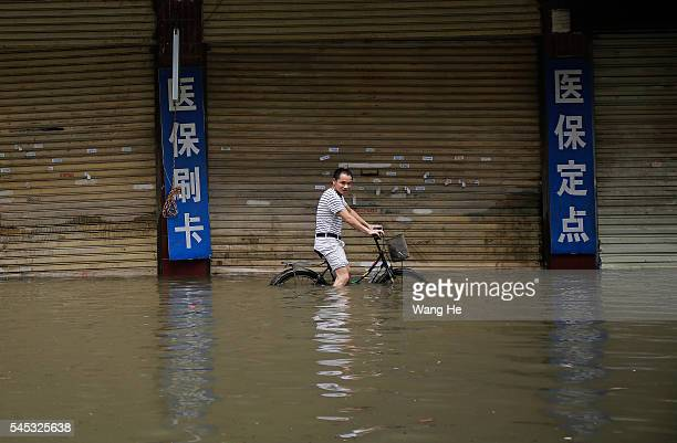 Man riding a bicycle in the flooded of South Lake Community Wuhan Hubei Province of China on 7 July 2016