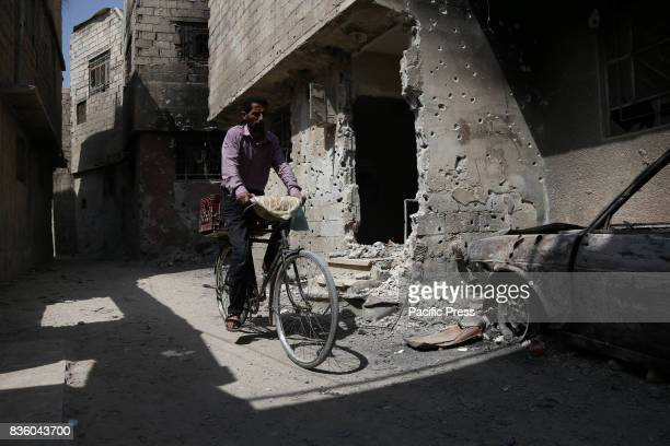 A man riding a bicycle passes by a destroyed place in Zamalka a city controlled by Syrian opposition forces in the eastern Ghouta