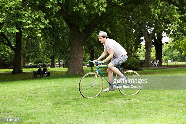 man riding a bicycle through the park