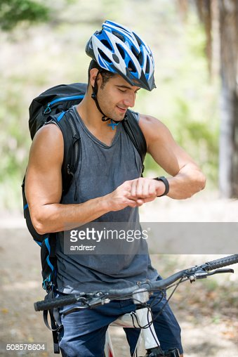 Man riding a bike and using a smart watch : Stock Photo