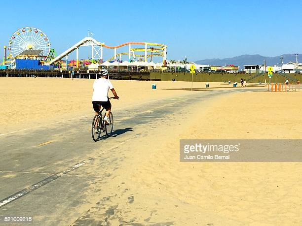 Man riding a bike near the iconic Santa Monica Pier in the County of Los Angeles California