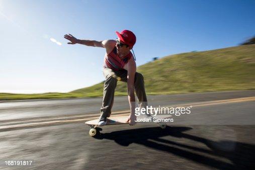 A man riding a lonboard skateboard.