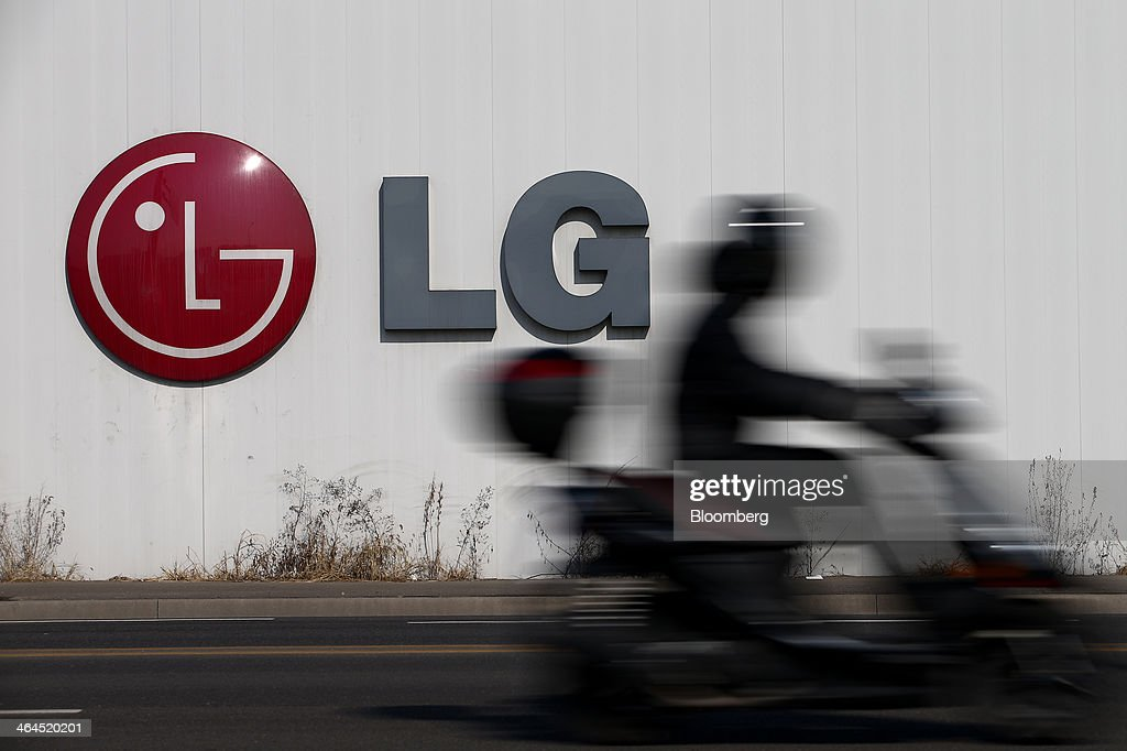 A man riding a motorcycle drives past an LG Electronics Inc. logo in Seoul, South Korea, on Wednesday, Jan. 22, 2014. LG Electronics, the worlds second-largest seller of televisions, is scheduled to announce fourth-quarter earnings on Jan. 27. Photographer: SeongJoon Cho/Bloomberg via Getty Images