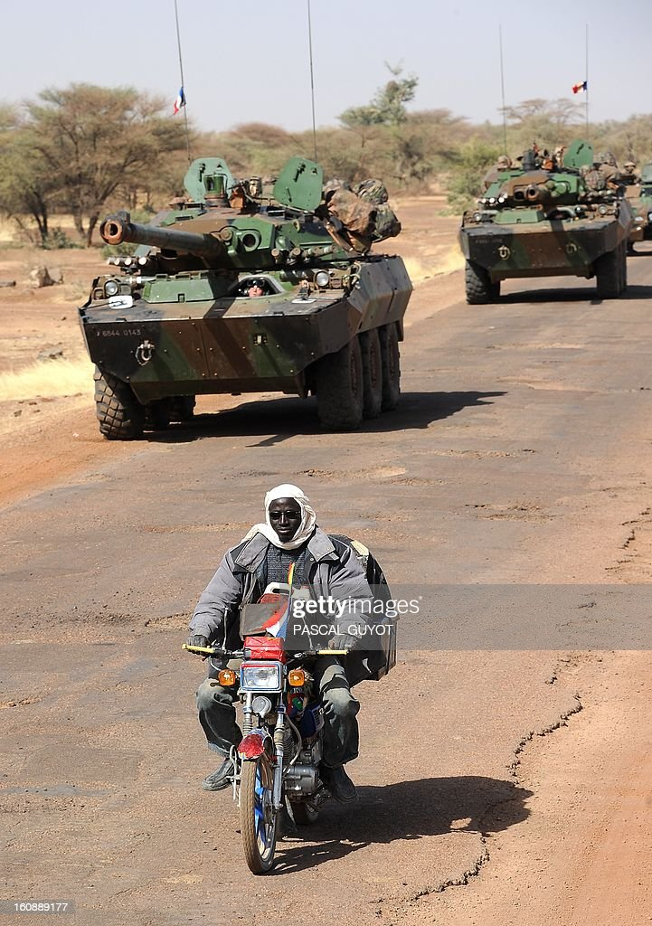 A man riding a motorcycle passes by a convoy of French army vehicules heading toward Gao on February 7, 2013 on the road from Gossi. Four Malian civilians were killed by a landmine in territory reclaimed from Islamist rebels, police said as France mulled handing over its four-week-old intervention to UN peacekeepers.