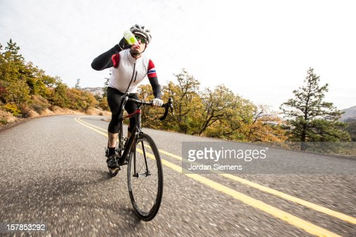 A man riding a road bike along a scenic road. : Stock Photo