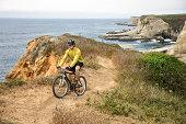 Man riding bicycle along coast