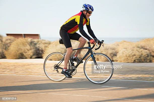 Man riding bicycle by sea