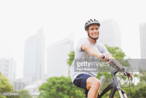 Man riding bicycle in urban park : Stock Photo
