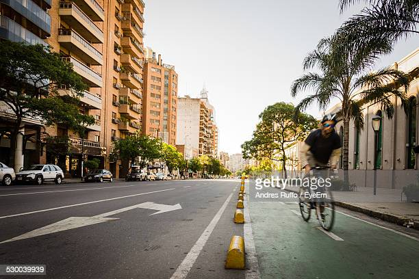 Man Riding Bicycle On City Street Against Clear Sky