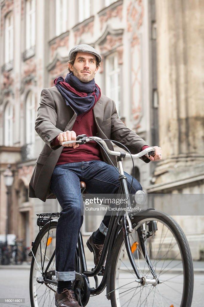Man riding bicycle on city street : Stock Photo