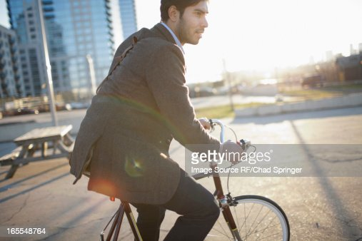 Man riding bicycle on city street : Stock Photo