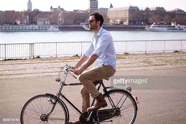Man riding bicycle on riverbank