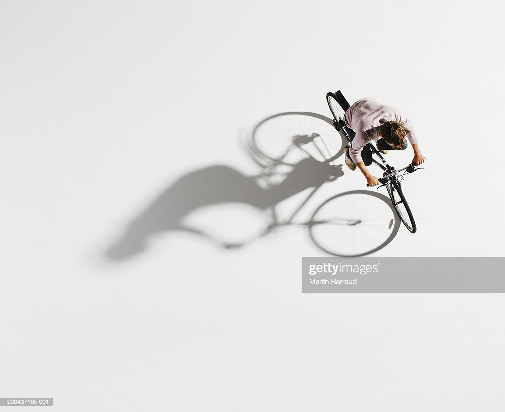 Man riding bicycle on white background, overhead view