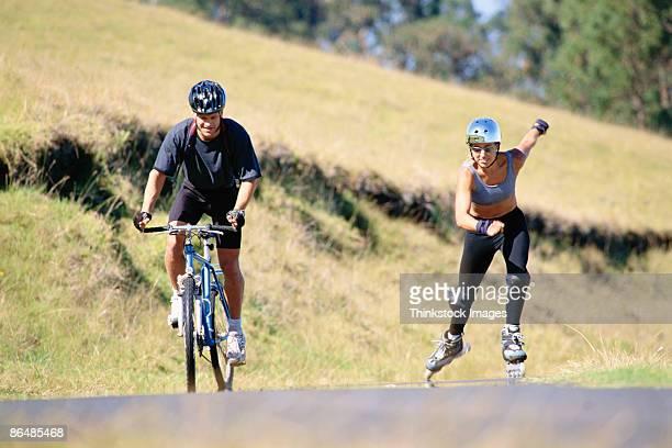Man riding bicycle racing woman inline skating