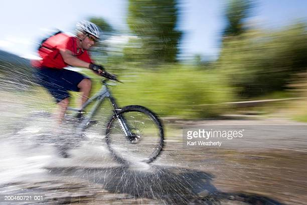 Man riding bicycle through stream (blurred motion)