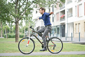 Man riding bicycle with arms outstretched