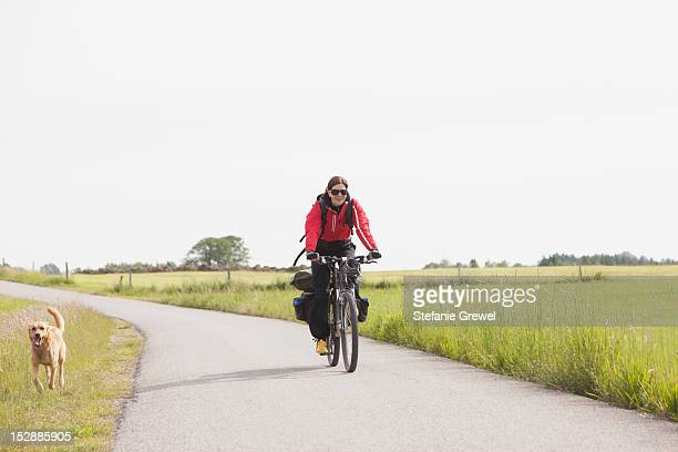Man riding bicycle with dog