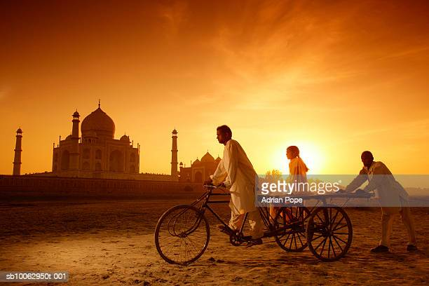 Man riding bicycle with girl sitting on trailer and man pushing from behind, Taj Mahal in background, sunset
