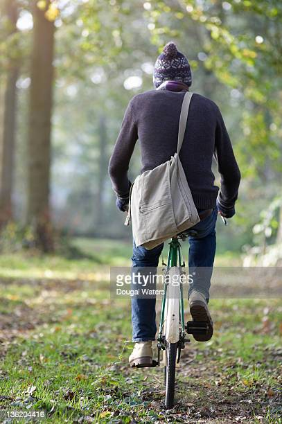 Man riding bike along path in forest.