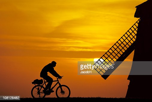 Man Riding Bike at Sunrise Near Windmill