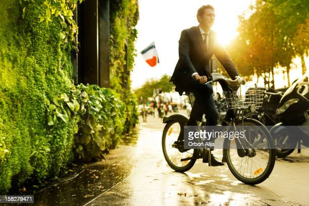 Man riding bike in front of vertical garden