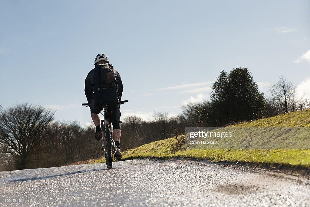 Man riding bike on countryside road : Stock Photo
