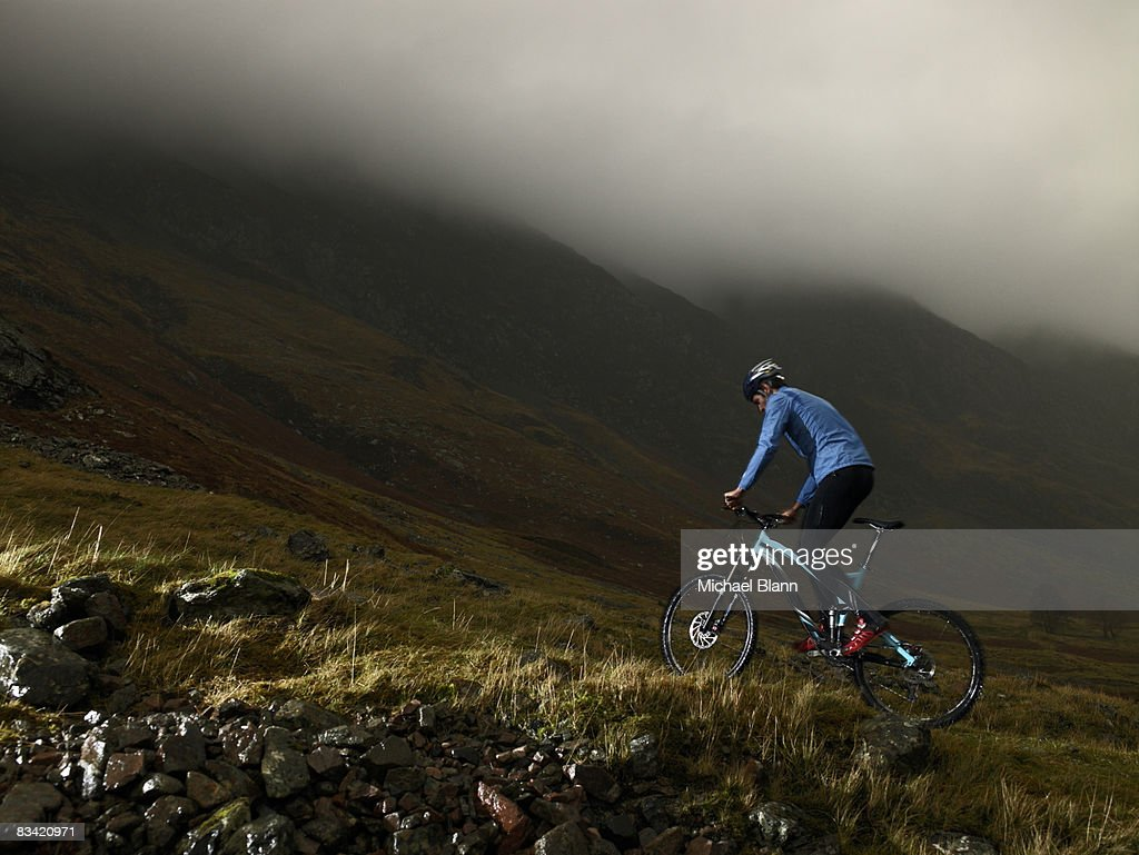 Man riding bike up mountain : Stock Photo