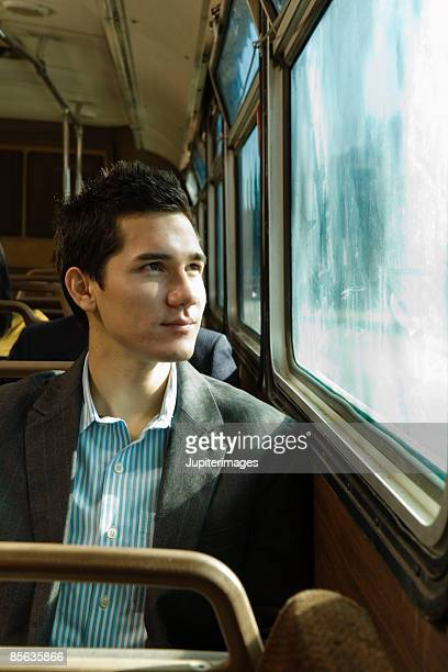 Man riding bus looking out window