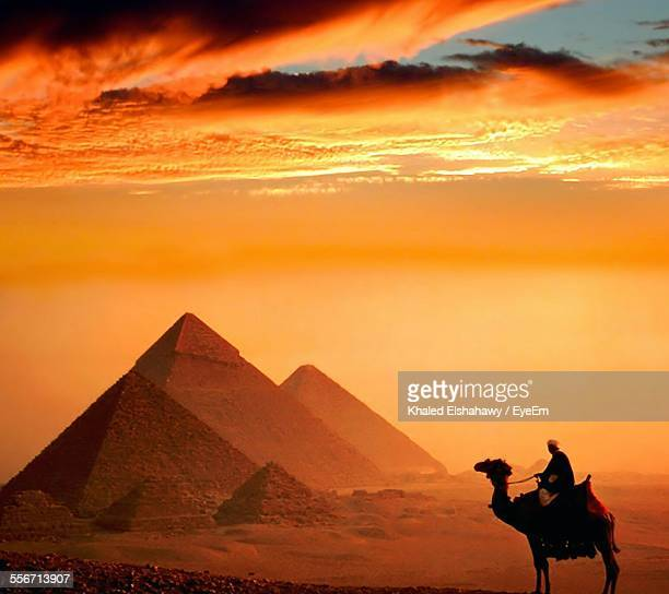 Man Riding Camel By Pyramids Against Orange Sky