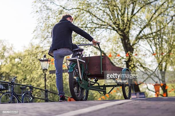 Man riding cargo bike onto bridge
